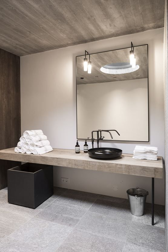 a minimalist industrial bathroom with stone tiles, concrete walls, a rough wooden vanity, a large mirror and lamps