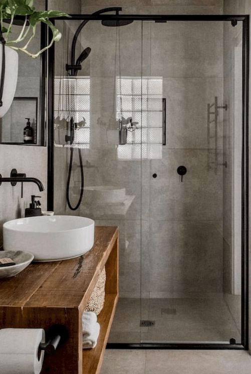 a modern industrial bathroom done with concrete, with a glass-enclosed shower space, a wooden vanity, a round sink and black fixtures