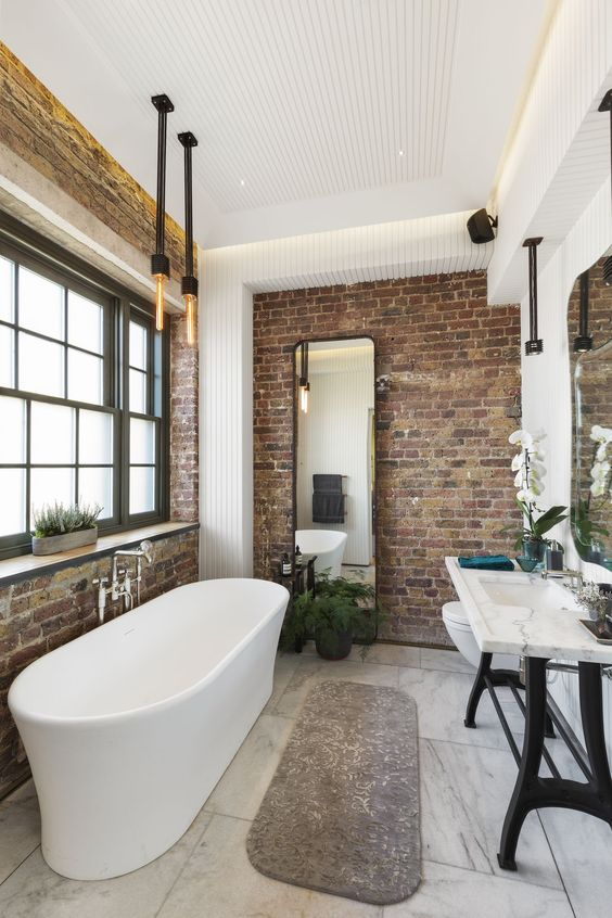 a modern industrial bathroom with brick walls, a stone sink on a stand, a free standing tub, exposed pipes and bulbs