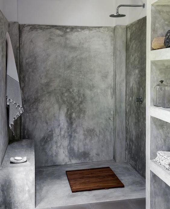 a modern industrial bathroom with concrete walls and a floor, a built-in shelving unit and exposed pipes