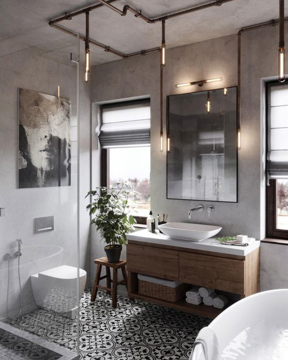 a modern industrial chic bathroom with concrete walls, printed tiles, a wooden vanity, exposed pipe lamps, chic appliances