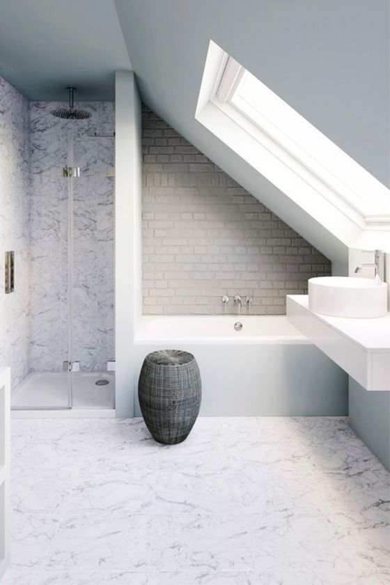 a neutral attic bathroom with marble tiles, faux brick, a basket for storage and a skylight and a floating vanity