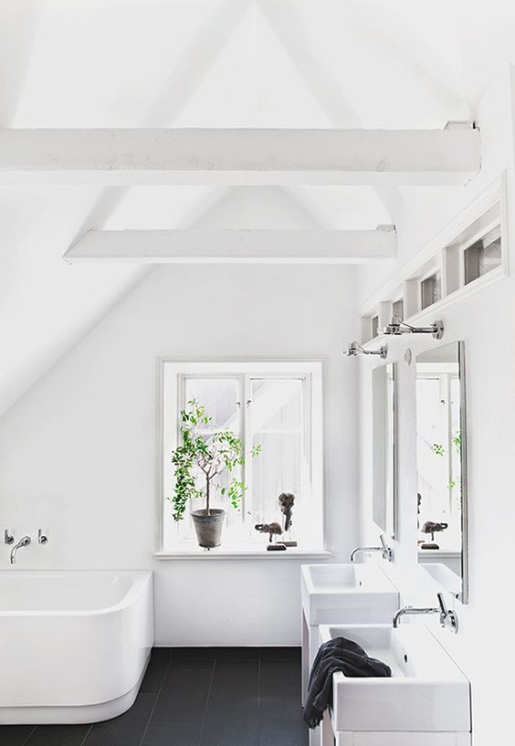 a pure hwite attic bathroom with a black tile floor, two sinks and a curved bathtub