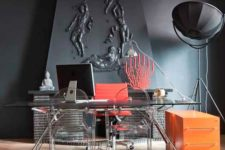 a quirky home office with graphite grey walls and a lamp, an industrial desk and acrylic chairs and touches of coral pink