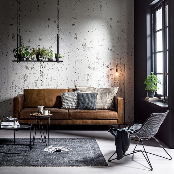 a simple industrial living room with shabby walls, hairpin leg coffee tables and industrial floor lamps