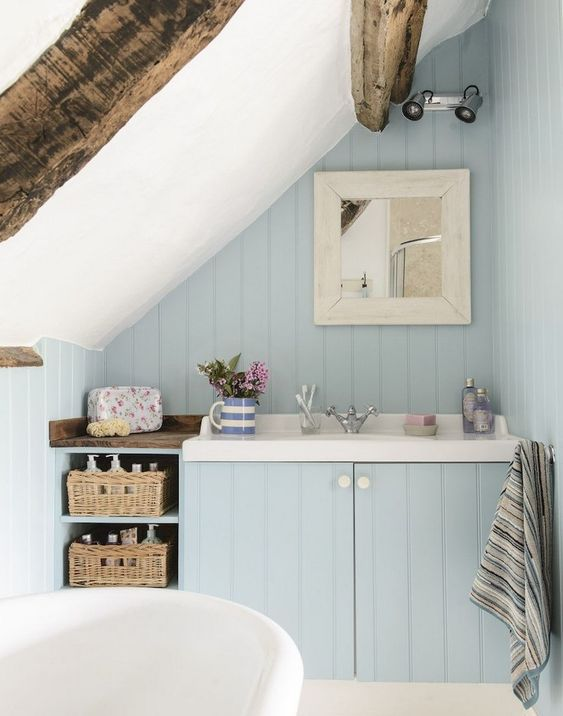 a small powder blue attic bathroom with wooden beams, baskets for storage and a free-standing tub