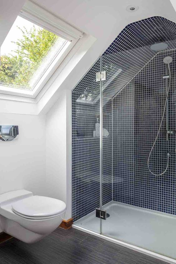 a tiny attic bathroom with navy tiles and white grout, a grey floor and a skylight