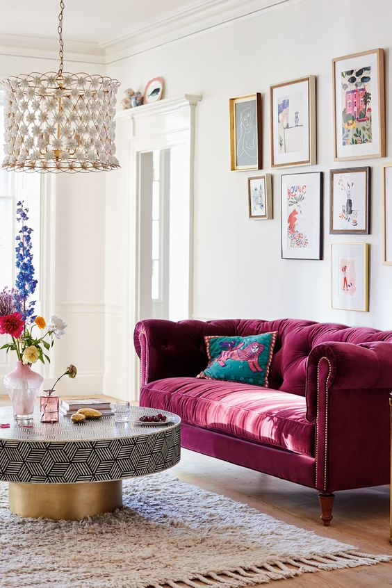 a tufted burgundy sofa is a bold and refined statement in the space and it will work for all the seasons