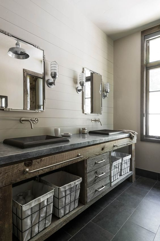 a vintage industrial bathroom with beadboard walls, a rough wood and stone vanity, stone sinks, exposed pipes and sconces