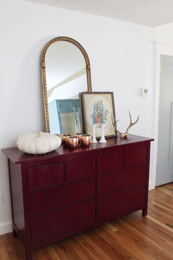 a vintage-inspired sideboard painted burgundy for the fall, with antlers and a pumpkin