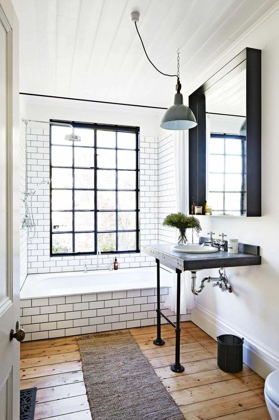 a vintage meets industrial bathroom with white subway tiles, a wooden vanity, a large mirror, pendant lamps