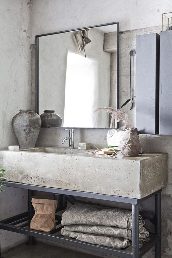 a wabi-sabi meets industrial bathroom with concrete walls, a concrete vanity with metal legs, mirrors and concrete vases
