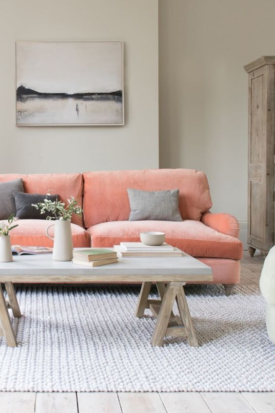 a welcoming living room with dove grey walls, a coral pink sofa, a concrete coffee table, an artwork and a wooden clsoet