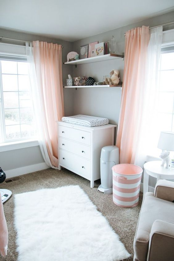 an airy dove grey and light coral nursery, with white furniture and a rug, with coral textiles and greys