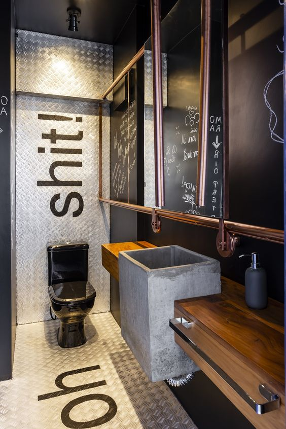 an industrial bathroom with black walls, white tiles, a wooden vanity, a concrete sink, a mirror in a copper frame and a black toilet