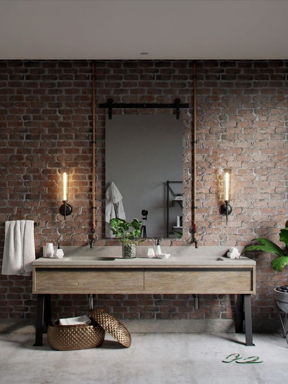 an industrial bathroom with brick walls, a wooden vanity with a stone sink, exposed pipes and wall sconces