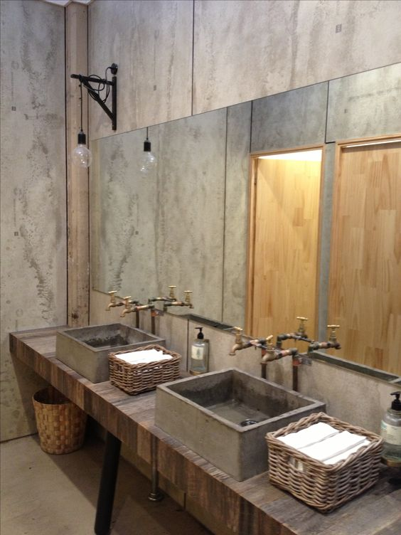 an industrial bathroom with concrete walls, a wooden vanity, concrete sinks and a large mirror plus vintage exposed pipes