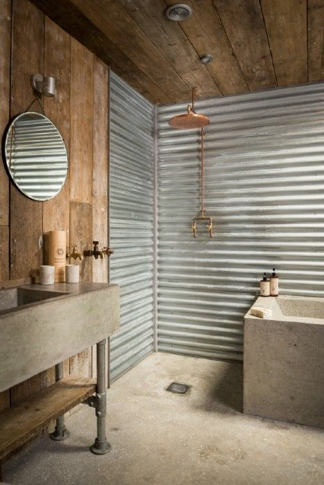 an industrial bathroom with rough wood and corrugated steel, a stone vanity and bathtub, exposed pipes and lamps