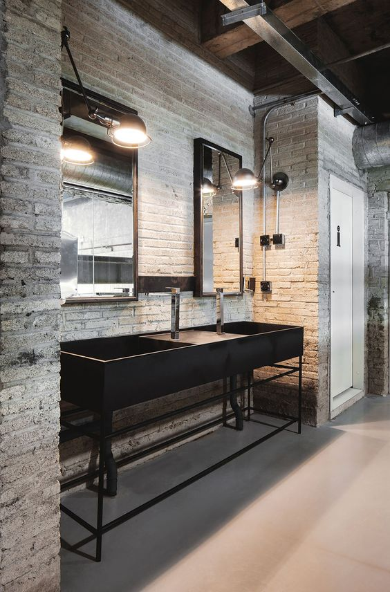 an industrial bathroom with whitewashed walls, black metal vanity with sinks, mirrors, exposed pipes and lamps