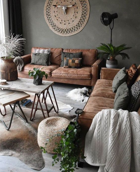 an industrial boho living room with leather sofas, potted plants, hairpin leg coffee tables and jute decor