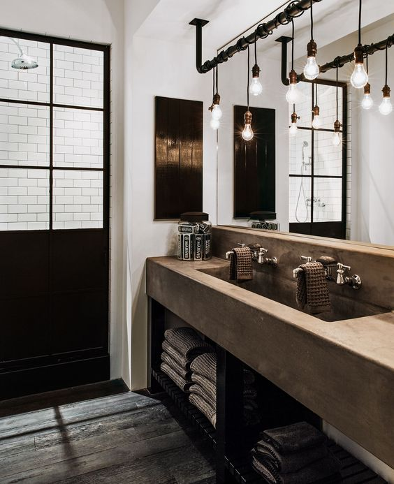an industrial chic bathroom with a glazed shower space, a concrete vanity with a double sink, a rough wooden floor, exposed pipes and bulbs