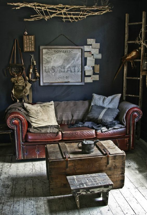 an industrial living room with a leather sofa, a shabby wooden chest and stool and some vintage art