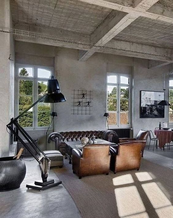 an industrial living room with retro touches, a metal floor lamp, leather furniture and concrete walls and floor