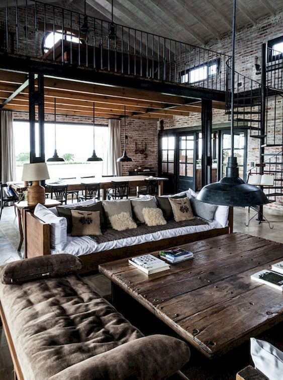 an industrial living space with some sofas and upholstered benches, a wooden coffee table plus retro pendant lamps