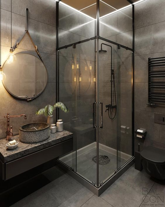 an industrial modern bathroom clad with grey tiles, with a glazed shower space, a floating vanity, copper faucets and exposed pipes