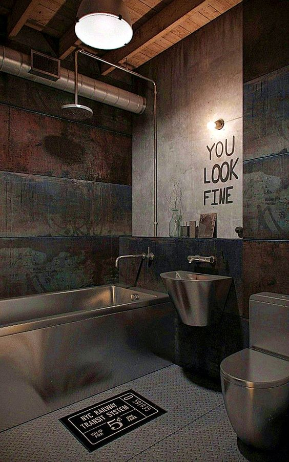 an industrial modern bathroom with concrete and rough wood walls, exposed pipes, lights and metal appliances