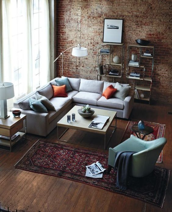 brick walls, rich-colored wood floors, an industrial piping open shelving unit and a metal and wood coffee table