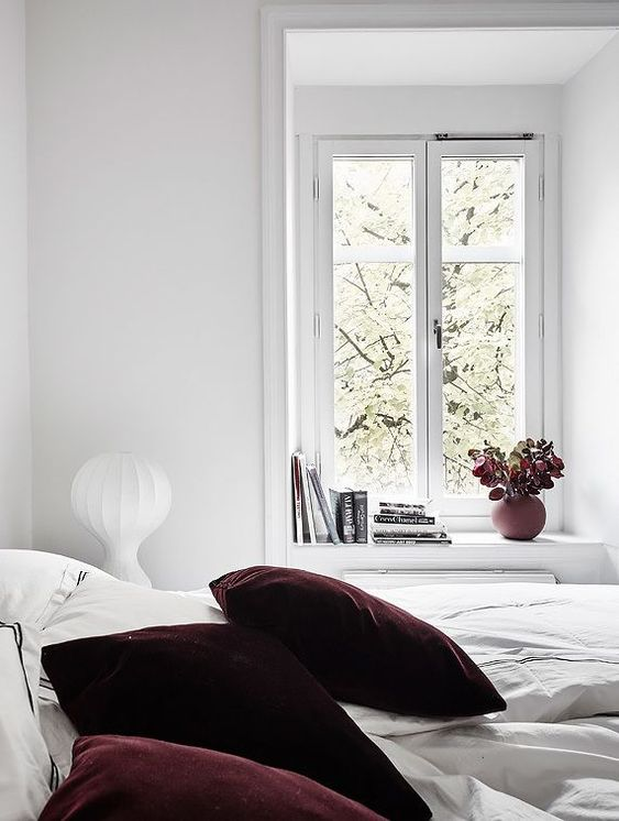 deep purple and burgundy velvet pillows will spruce up your neutral bedroom and hint on the season