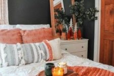 graphite grey walls, white furniture, coral textiles, boho pillows and greenery in vases create a welcoming ambience in the space