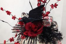 a Halloween centerpiece of a painted pumpkin, black glitter skeleton hands, red blooming branches, blooms and a crow on top