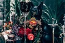 a Halloween tablescape done in black, with a black cat figurine and a bold floral centerpiece with berries and dried touches