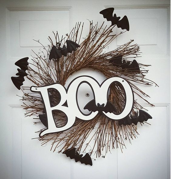 a Halloween twig wreath with black bats and black and white letters is a small and cool idea to decorate your front door in a creative way