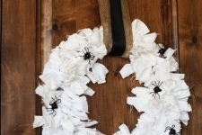 a Halloween wreath covered with white fabric stripes, with black spiders and a burlap and black ribbon is simple and cool