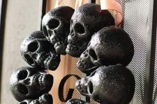 a Halloween wreath of glitter black skulls and an orange bow on top is a classic decor idea for Halloween