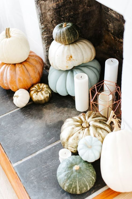 a Thanksgiving fireplace with stacked heirloom pumkins and pilalr candles in lanterns and without them