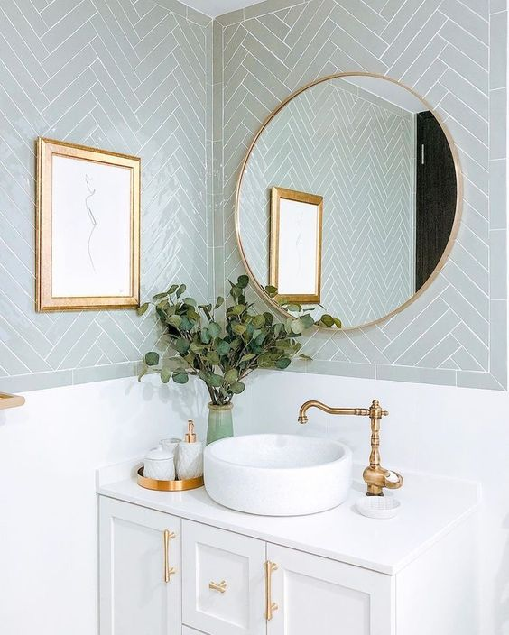 a beautiful bathroom with pale blue chevron tiles, a white vanity, gold handles, a round mirror in a gold frame, gold fixtures and an artwork in a gold frame