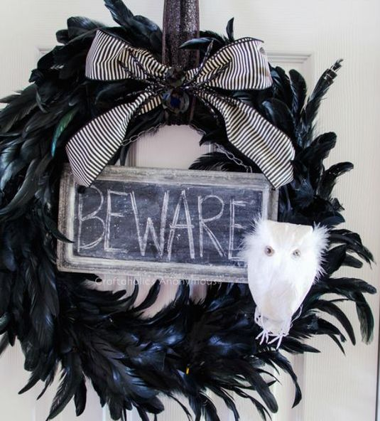 a black Halloween wreath of black feathers, a sign, a white owl and a black and white striped bow is amazing for decor
