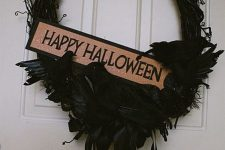 a black Halloween wreath of vine, with blackbirds, feathers and ribbons plus a mini sign is a creative and bold solution