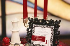 a black and red dessert table with a tray with red candles, chess, cupcakes topped with photos and a refined black frame