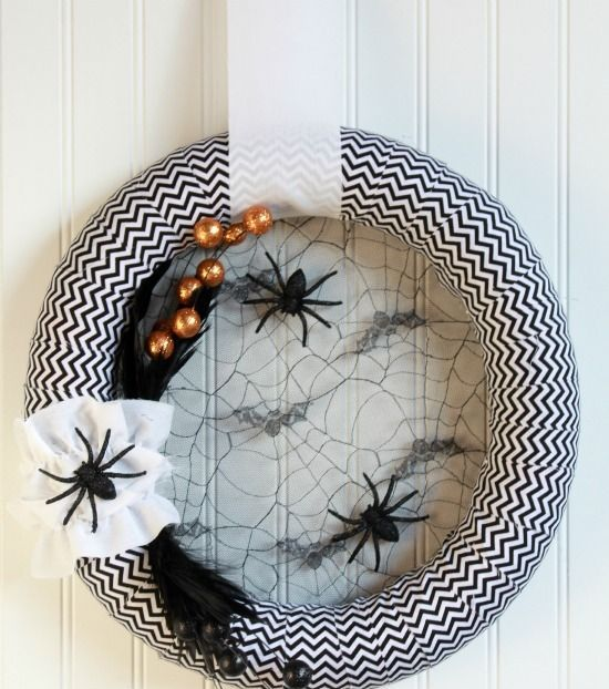 a black and white Halloween chevron wreath with spider webs, spiders and feathers plus oversized beads is a cool idea to decorate your front door
