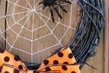 a bold Halloween wreath of black vine, a spider web and a black spider plus an orange polka dot bow for an accent