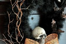 a bold Halloween wreath of faux fur, gilded twigs, a skeleton hand, a skull and an orange mesh bow is amazing