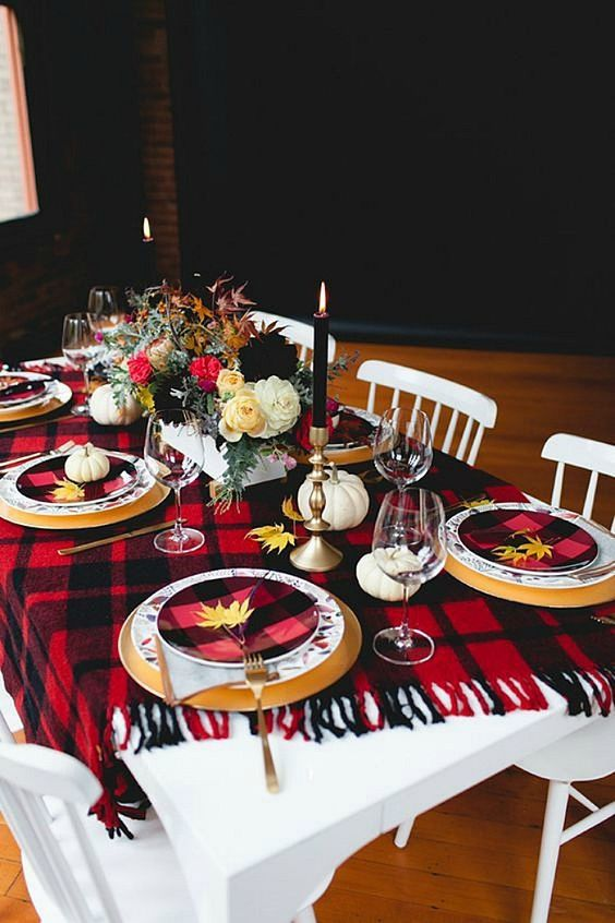 a bold Thanksgiving tablescape with a plaid blanket and plates, tall candles, fall leaves and pumpkins plus florals