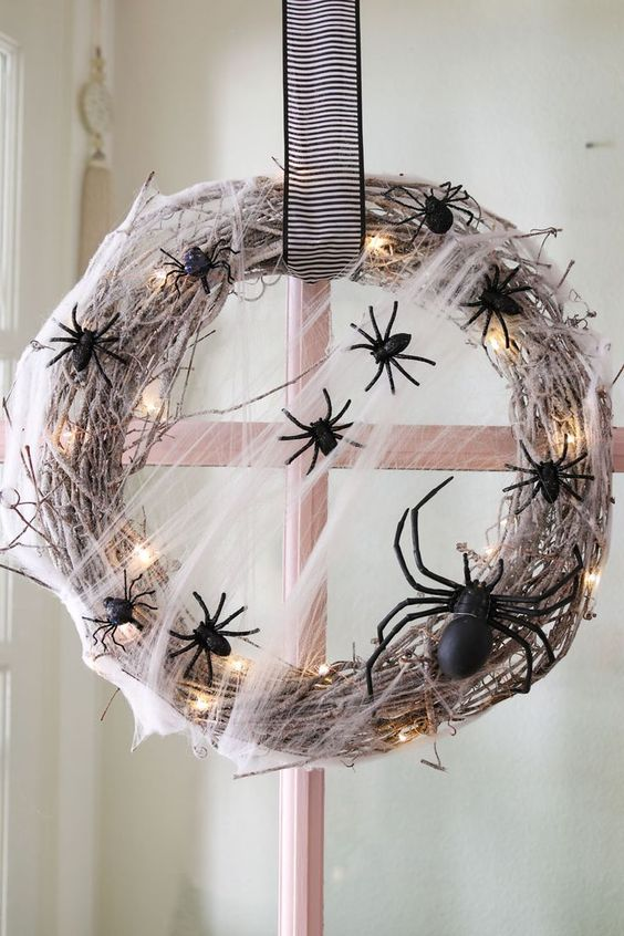 a bold and pretty Halloween wreath of whitewashed vine, LED lights, black spiders and a striped bow is a lovely idea to go for