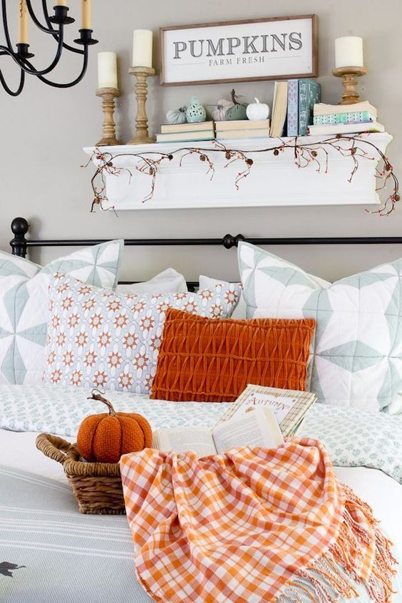 a bold orange pillow, a plaid blanket and a fabric pumpkin in a basket for a fall touch in the living room