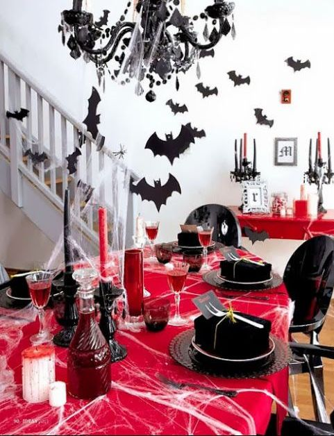a bold red and black Hallloween tablescape with spiderwebs, red vases and goblets, black plates and boxes, bats and a black chandelier